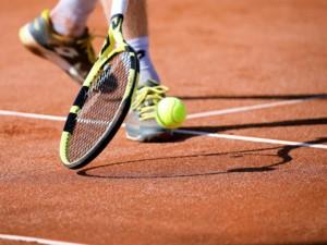Bild von Tennisschläger mit Ball auf Tennisplatz